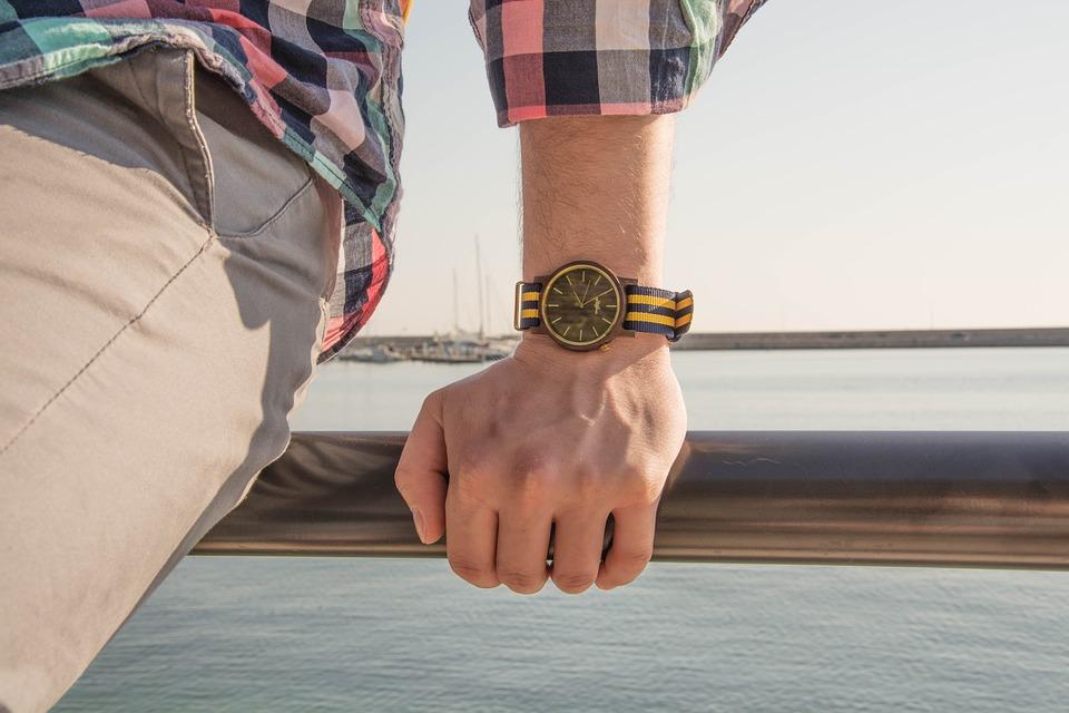 Hombre con reloj de madera, en la costa